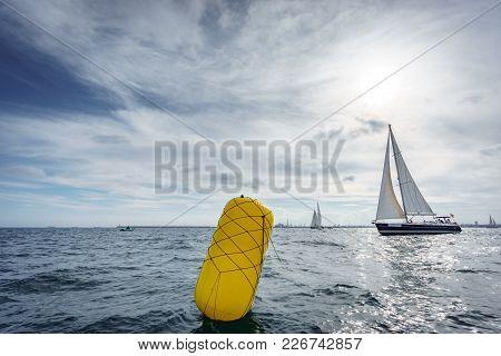 Wide Angle View Of Buoy And Sailing Boat In The Sea