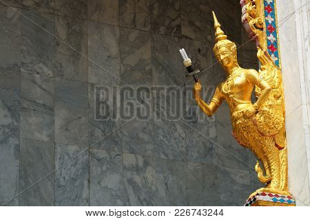 Golden Statue Of Male Angel, Half Upper Body Is Human And Half Lower Part Is Bird, Holding Compact F