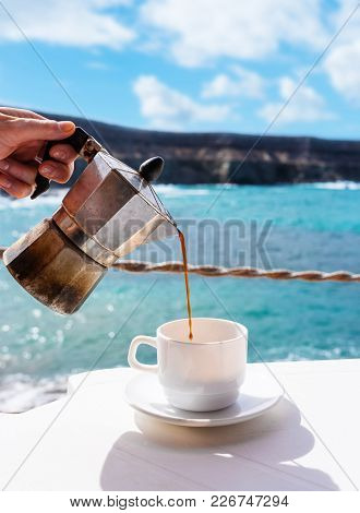 Close-up Outdoor Shot Female Hand Holding Moka Pot While Pouring Hot Coffee Into White Cup On Table