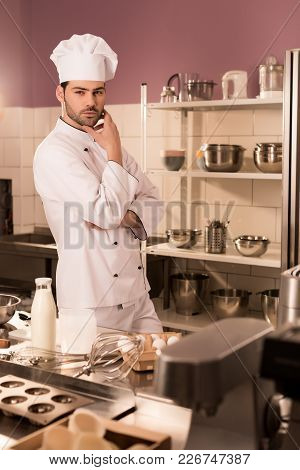 Pensive Confectioner Standing At Counter In Restaurant Kitchen