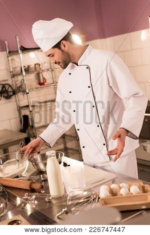 Confectioner In Chef Hat Making Dough In Restaurant Kitchen