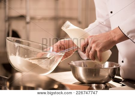 Partial View Of Confectioner Adding Milk Into Dough In Restaurant Kitchen
