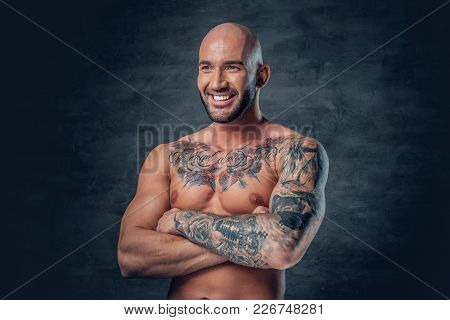 Portrait Of Smiling Shaved Head, Muscular Male With Crossed Arms And Tattoos On His Suntanned Body.