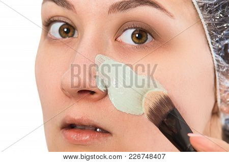 Skin care concept. Scrub for cleansing pores of face. Girl putting cleansing mask on her face closeup isolated. poster