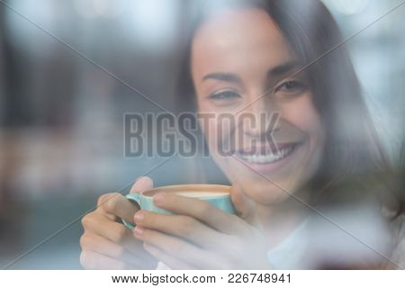 Peaceful Mood. Merry Cheerful Sincere Woman Embracing Cup While Staring Aside And Smiling