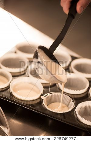 Cropped Shot Of Confectioner Pouring Dough Into Baking Forms