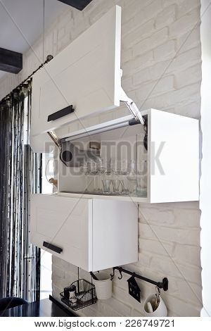 Completely Opened White Kitchen Cabinet With Wineglasses And Glasses On Shelf
