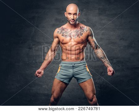 Shaved Head Shirtless Muscular Male With Tattooed Body Dressed In A Sport Short Over Grey Background