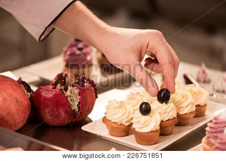 Cropped Shot Of Confectioner Decorating Sweet Cupcakes