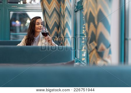 Self Assured. Meditative Good Looking Charming Woman Drinking Wine And Sitting At Cafe While Staring