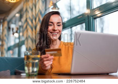 Convenient Payment. Merry Good Looking Happy Woman Holding Credit Card While Looking At Screen And S
