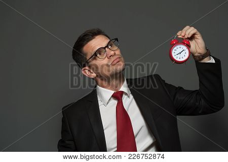 Young Male Manager In Formal Attire And Glasses Holds Clock On A Gray Background