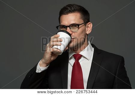 Portrait Of Young Male Manager In Formal Attire And Glasses Is Drinking Coffee On Gray Background