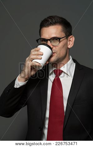 Portrait Of Handsome Businessman Wearing Glasses And Formal Attire Drinking Coffee On Gray Backgroun
