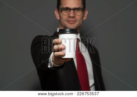 Close-up - Young Male Manager In Formal Attire And Glasses Holds Mug Of Coffee On Gray Background