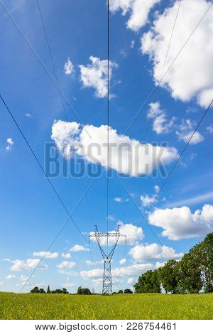 Power Pylons And High Voltage Lines In The Green Grass Field With Blue Sky And Cloud.