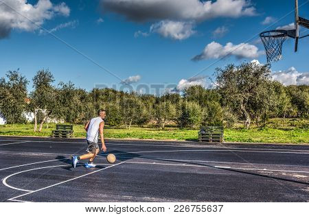Basketball Player Dribbling To The Hoop In A Playground On A Cloudy Day