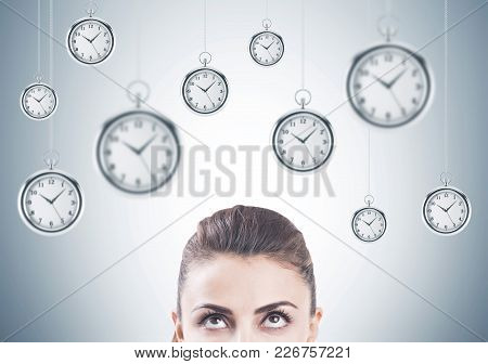 Portrait Of An Attractive Young Brunette Woman Looking Upwards At Many Stopwatches Hanging Against A