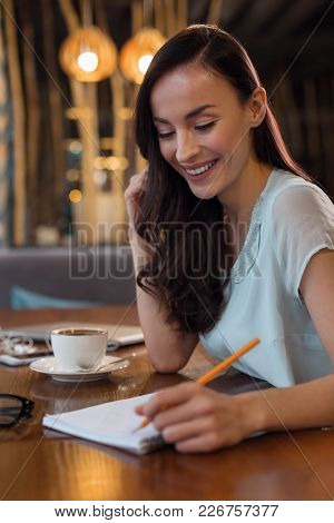 My Journal. Pensive Joyful Good Looking Woman Smiling While Staring Down And Using Pencil