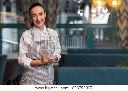 Tell Your Desire. Skillful Young Merry Waitress Using Notebook While Smiling To Camera And Standing