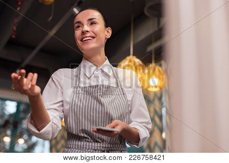 New Menu. Optimistic Energetic Nice Waitress Moving Hand While Grinning And Receiving Order