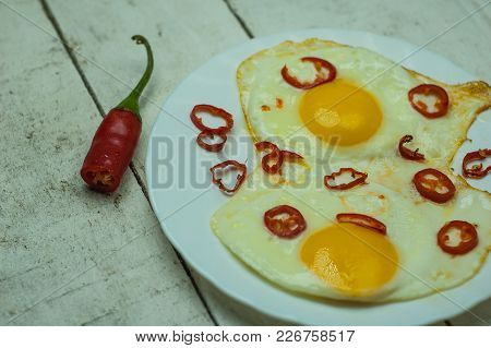 Two Fried Eggs With Chili Pepper On White Table.