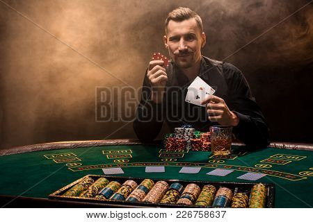 Handsome Poker Player With Two Aces In His Hands And Chips Sitting At Poker Table In A Dark Room Ful
