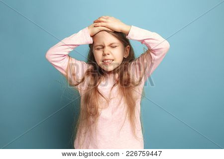 The Headache. The Sad Teen Girl With Headache Or Pain On A Blue Studio Background. Facial Expression