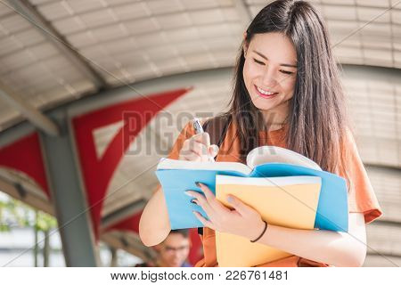 Young Woman With Backpack Hold Notebook Standing In University