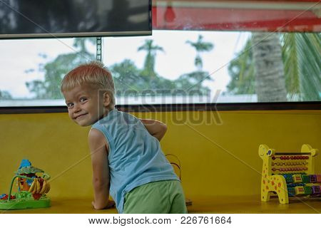Handsome Preschool Boy Plays Toys In Playroom. Palm Trees Background