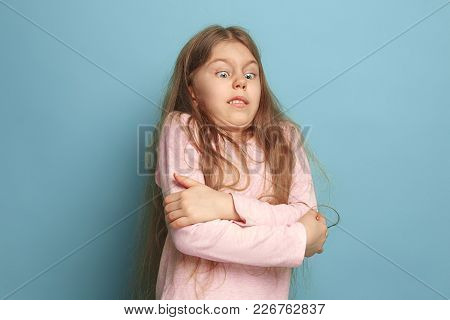 The Surprise. The Surprised Teen Girl On A Blue Studio Background. Facial Expressions And People Emo
