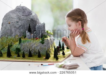 Children Work On Model Building School Project. Kids Build Miniature Scale Model Mountain For Geogra