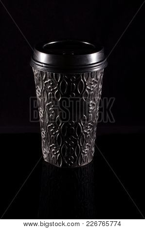Black Paper Coffee Cup With Plastic Lid On The Black Background