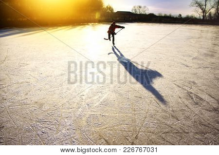 Hockey Player On Natural Ice In Gold Evening Light