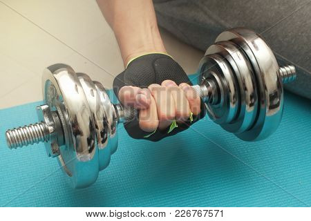 Sitting And Using His Right Hand Lifting Weights At The Shiny Steel,heavy Steel Dumbbell, Blue Cloth