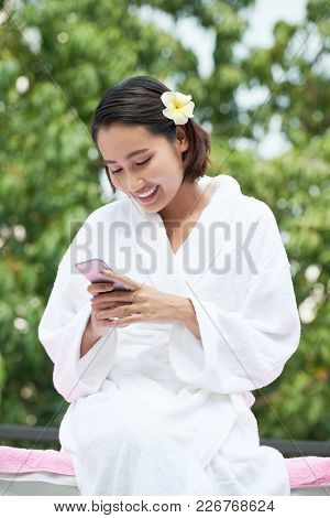 Pretty Smiling Young Woman In Soft Bath Robe Checking Smartphone
