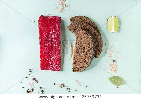 Piece Of Beetroot Marinated Salted Salmon With Sliced Rye Bread, Pink Salt, Pepper And Lime Over Lig