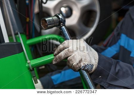 The Wizard Holds The Adjustable Wrench. The Man Is Repairing The Disc Brake Machine, Close-up. Disk