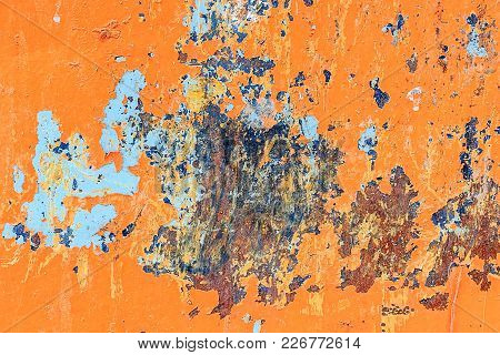 Orange Metal Background With Cracked, Peeling Paint With Stains Of Blue Paint And Rust Spots.
