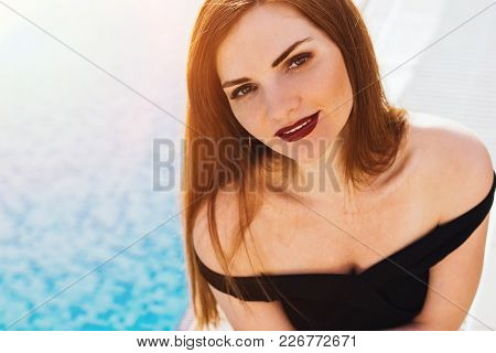 A Rich Attractive Woman In A Black Dress Is Enjoying A Luxurious Rest By The Pool