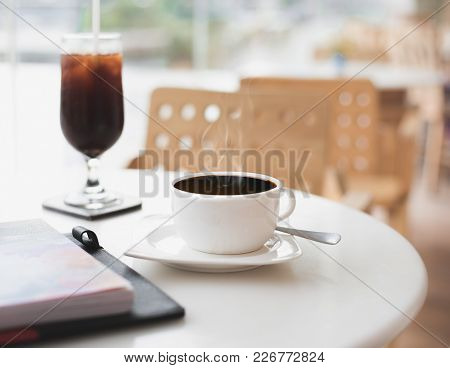 Hot Black Coffee Mug With Steam On Table At Empty Cafe/restaurant. Concept Of Loneliness, Isolation,