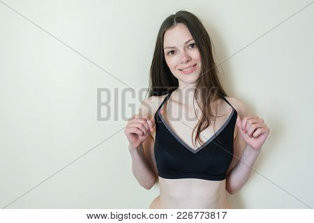 Brunette Woman With Long Hair Stands At The Wall And Looks At Camera. Hands Behind Her Back.