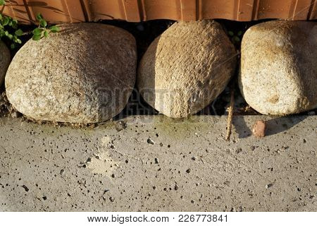 Three Large Stones In A Cement Floor Are A Confidence And Tranquillity Symbol, Landscape Design.