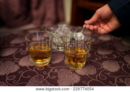 Man Putting An Ice Cube In A Glass Of Whiskey. Alcohol