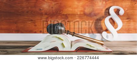 Open Law Book With Wooden Gavel And Paragraph Sign In A Lawyer Office With Copy Space On The Left Si