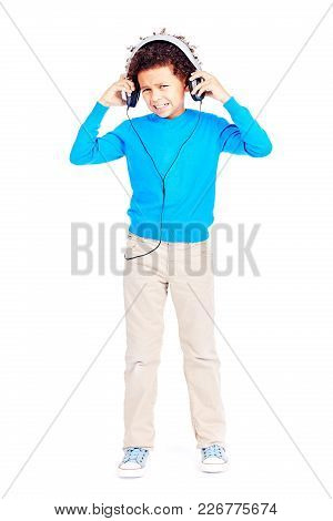 Portrait Of Cute Curly-haired Latin American Boy Annoyed With Music In His Headphones