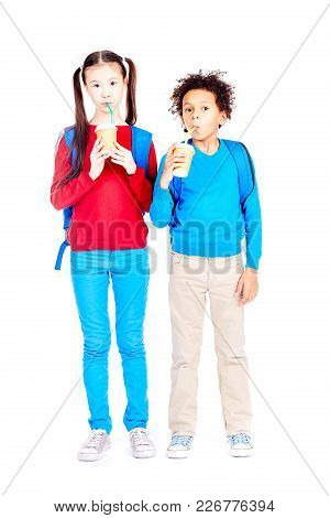 Portrait Of Asian Schoolgirl And Latin American Schoolboy Posing Together On White Background