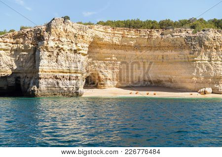 Hidden Remote Beach Covered With Limestone Walls. Kayak Left On The Beach By Tourists Went For Cave