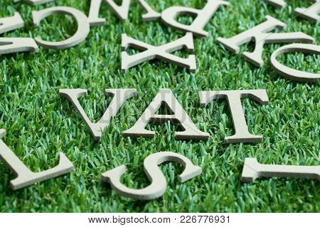 Wood Letter In Word Vat (abberviation Of Value Added Tax) On Artificial Green Grass Wit English Alph
