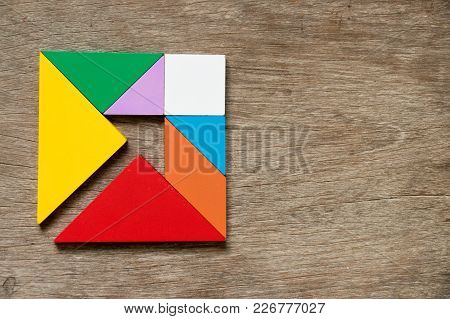 Colorful Tangram Puzzle In Square With Inside Arrow Direction Shape On Wood Background